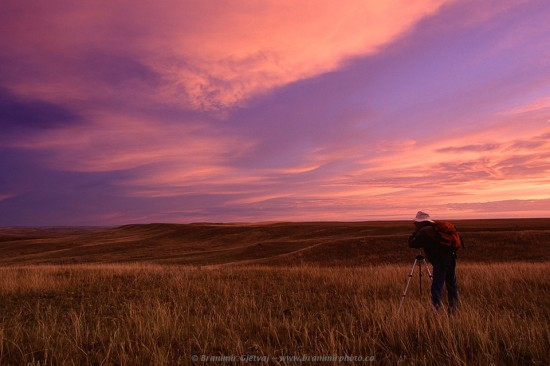 Photographer taking pictures of a prairie in Grasslands National Park at dawn