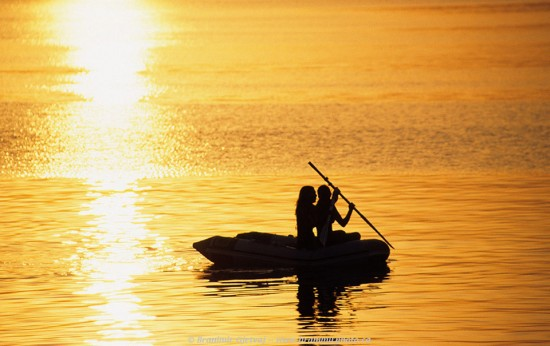 Two young women paddle in a rubber boat at sunset. Island of Mljet, Croatia