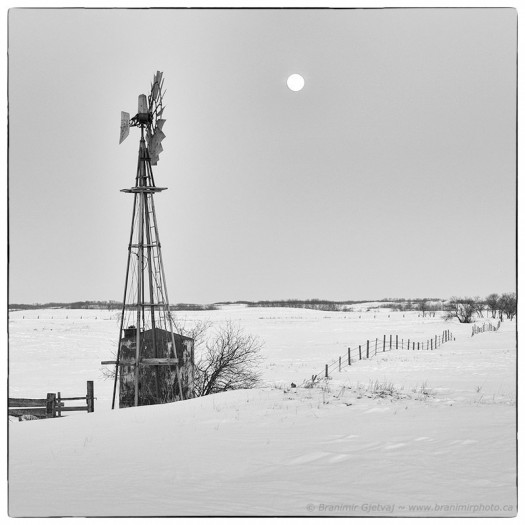 Windmill and moonrise over snow-covered fields