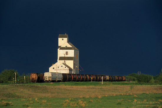 Grain elevator and freight train after a storm. Bulyea, Saskatchewan